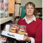 Church member and food bank volunteer Peggy Wilmot holds an arm full of food in the St. John the Divine Church basement