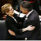 Ontario Finance Minister Charles Sousa embraces Premier Kathleen Wynne after delivering the provincial budget