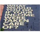 Huge tarpaulin viewed from the air that reads What would you do if your income were taken care of?
