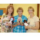 Linda Woods, Laurel Kelley and Sarnia's Ann Carr hold up several Dolls of Hope during a workshop