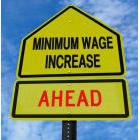 Mock road sign reading: Minimum Wage Increase Ahead