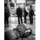Homeless person lying on the sidewalk beside unconcerned passersby