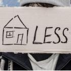 Person holding a sign with an image of a home - followed by the word 'less'