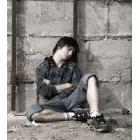 An apparently homeless youth sitting on a sidewalk