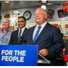 Premier Doug Ford behind a sign reading