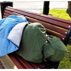 An apparently homeless person lying on a bench