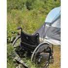Wheelchair outside a tent in a homeless camp