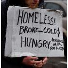 Homeless person with a sign reading