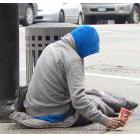 Homeless person sitting on a sidewalk with a cup in his hand