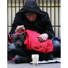Homeless man on the sidewalk keeping his dog warm on his lap