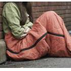 An anonymous woman in a sleeping bag on the pavement
