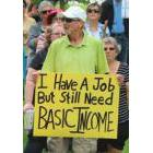 Person holding a poster that reads: I Have A Job But Still Need BASIC INCOME