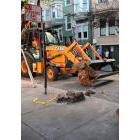 A San Francisco Public Works crew removes boulders from a sidewalk along a street in San Francisco