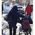 Homeless person with their belongings walking on a snowy street